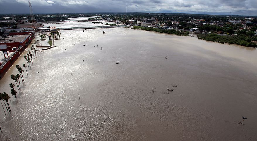 A swollen Rio Grande, driven by dam releases upstream and rain-swollen tributaries following last week's Hurricane Alex, pushes against International Bridge 1, foreground, which remains closed, and International Bridge 2, background, still open, Friday, July 9, 2010, in Laredo, Texas. The river has crested, but is not expected to drop for several days. (AP Photo/Eric Gay)