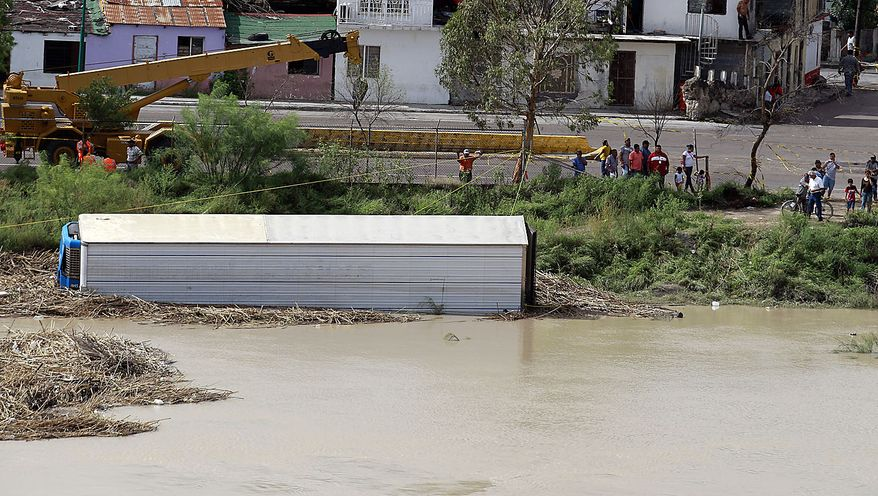 A trailer that floated down the Rio Grande, driven by dam releases upstream and rain-swollen tributaries following last week's Hurricane Alex, is secured to the bank, Friday, July 9, 2010, in Nuevo Laredo, Mexico. The river has crested, but is not expected to drop for several days. (AP Photo/Eric Gay)