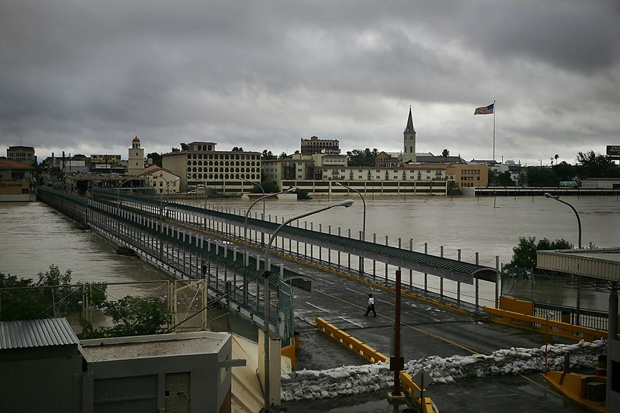 A woman walks along international Bridge 2 that connects Nuevo Laredo, Mexico, bottom, and the U.S. city of Laredo, top, separated by the swollen Rio Grande as seen from Mexico, Friday July 9, 2010. A tropical depression that came ashore just north of the mouth of the Rio Grande on Thursday was expected to add 6 inches to 8 inches of rain to rivers and reservoirs in south Texas and northern Mexico already swollen from the heavy rains dropped by Hurricane Alex. (AP Photo/Miguel Tovar)
