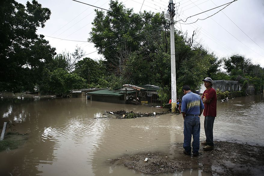 Men stand outside their flooded homes in Nuevo Laredo, Mexico, Friday July 9, 2010. A tropical depression that came ashore just north of the mouth of the Rio Grande on Thursday was expected to add 6 inches to 8 inches of rain to rivers and reservoirs in south Texas and northern Mexico already swollen from the heavy rains dropped by Hurricane Alex. (AP Photo/Miguel Tovar)