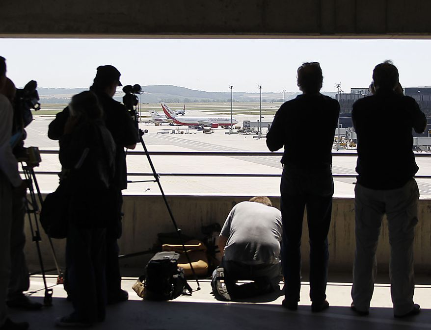 Media take pictures of a U.S., front, and a Russian plane, rear, believed to be carrying candidates for a 14-person spy swap as part of the largest spy swap since the Cold War have parked on the tarmac at Vienna's Schwechat airport on Friday, July 9, 2010. (AP Photo/Matthias Schrader)