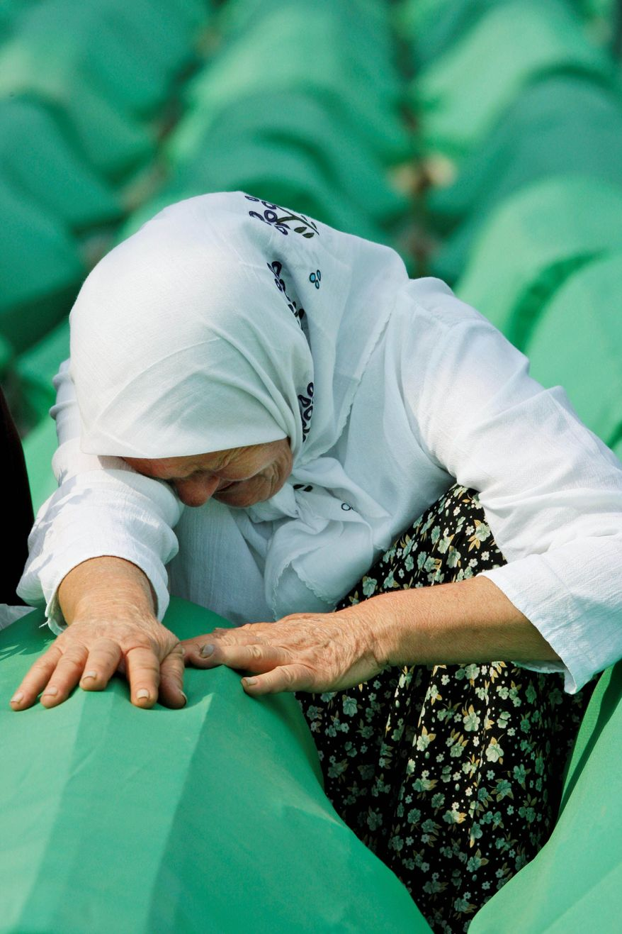A Bosnian Muslim woman weeps near the coffin of her relative, a Srebrenica victim, in Potocari on Sunday. Thousands gathered at the Potocari Memorial Center to mark the 15th anniversary of the 1995 Srebrenica massacre on Sunday. (Associated Press)