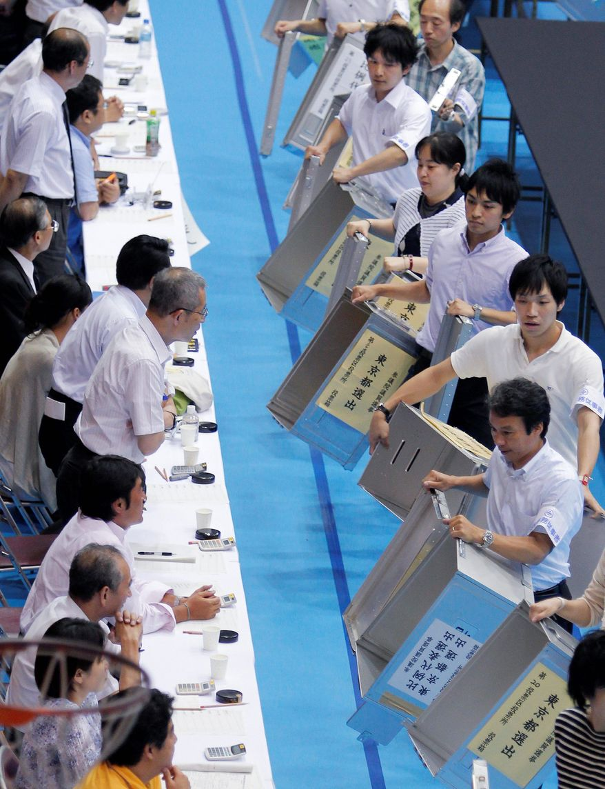 Election staff show empty ballot boxes to officials in the parliamentary upper house elections at a ballot counting center in Tokyo on Sunday. (Associated Press)