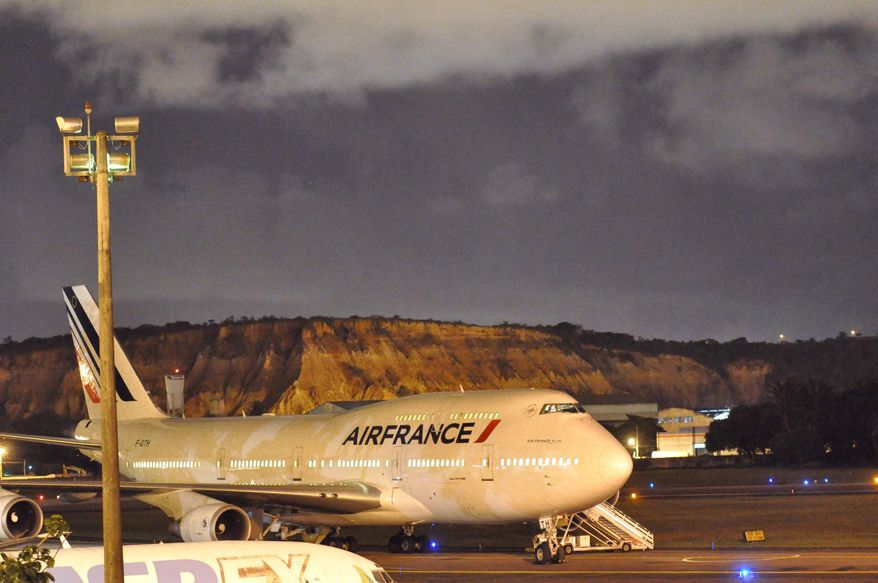 An Air France passenger jet sits on the tarmac in Recife, Brazil, on Saturday, July 10, 2010, after making an emergency landing because of a bomb threat. (AP Photo/Alexandre Gondim, JC Imagem)