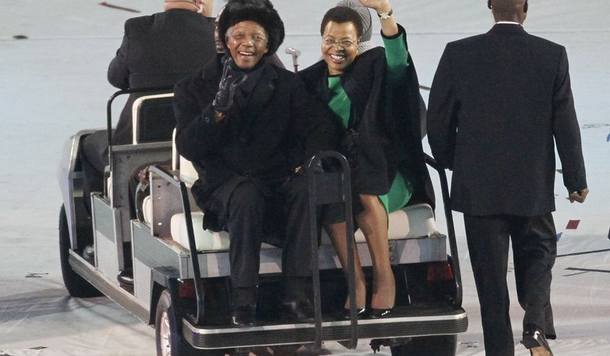 Former South African President Nelson Mandela (left) and his wife, Graca Machel, greet the crowd as they are driven across the field ahead of the World Cup final match between the Netherlands and Spain at Soccer City in Johannesburg on Sunday, July 11, 2010. (AP Photo/Eugene Hoshiko)