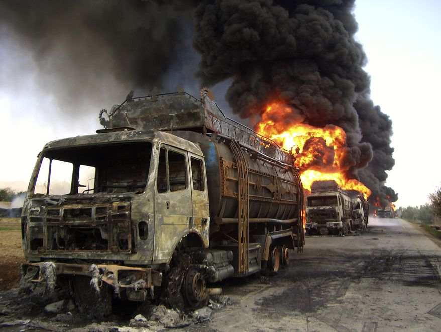 ** FILE ** Trucks carrying supplies to coalition forces burn after hundreds of people blocked a main road and set them on fire to protest what they said were civilian deaths in NATO operations in Logar province, west of Kabul, Afghanistan, on April 25, 2010. (AP Photo/Mohammed Obaid Ormur, File)