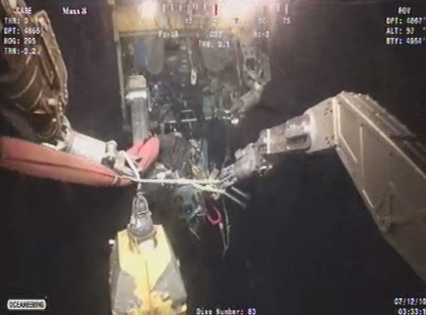 In an image made from video provided by BP PLC, underwater robots work on assembling equipment early on Monday, July 12, 2010, for containing the oil gushing from the damaged oil well in the Gulf of Mexico. A second robot is in the background. (AP Photo/BP)