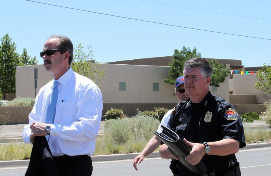 Albuquerque Mayor Richard Berry, left, and Police Chief Ray Schultz, right, leave a press conference near the scene of a deadly shooting in Albuquerque, N.M., on Monday, July 12, 2010. Police said a man entered a building and shot nine people, five of whom died. Police said the gunman was found inside the building dead of a self-inflicted gunshot wound. (AP Photo/Susan Montoya Bryan)