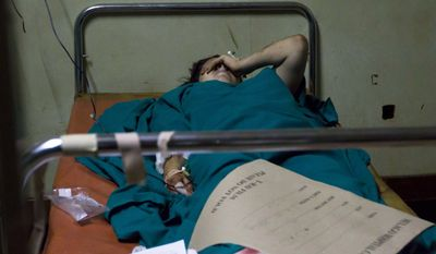 An American women lies injured in the emergency ward at the Mulago Hospital in Kampala, Uganda, on Monday, July 12, 2010, after bombs exploded at two sites in Uganda's capital late Sunday as people watched the World Cup final on TV. The blasts killed scores of people. (AP Photo/Marc Hofer)