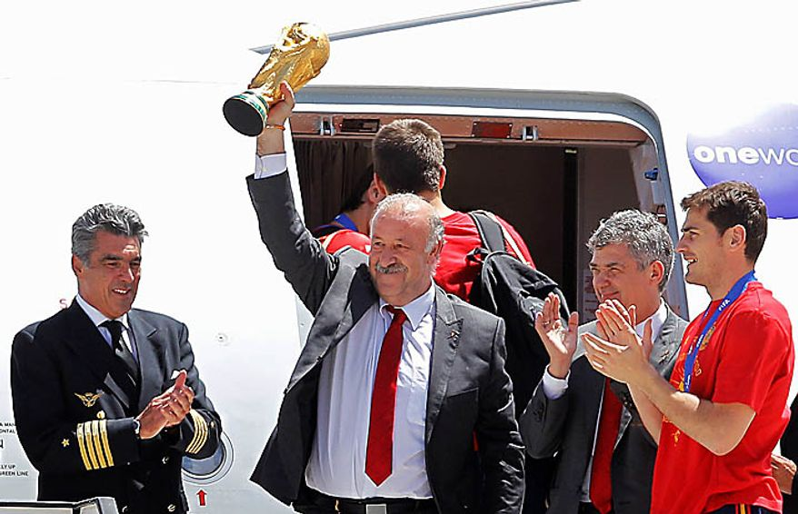 Spain's captain Iker Casillas, right, applauds as the team coach Vicente del Bosque, left, raises the World Cup trophy as they leave the plane at Madrid's Barajas airport on Monday, July 12, 2010. Spain won the World Cup after defeating the Netherlands 1-0 on Sunday. (AP Photo/Victor R. Caivano)