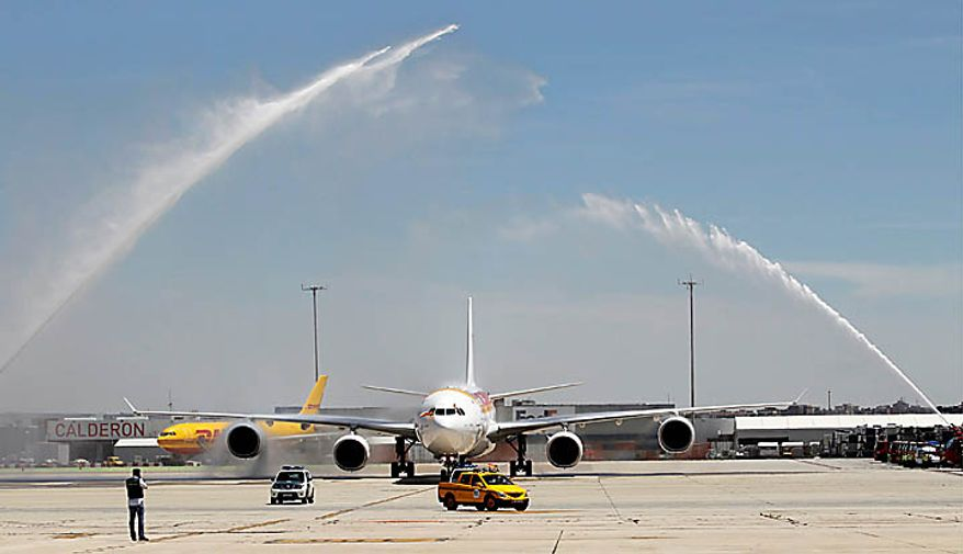 Firefighters spray a water fountain as they welcome the airplane carrying the Spanish soccer team in celebration after it landed at Madrid's Barajas airport on Monday, July 12, 2010.  Spain won the World Cup soccer tournament played in South Africa after defeating the Netherlands 1-0 on Sunday. (AP Photo/Armando Franca)