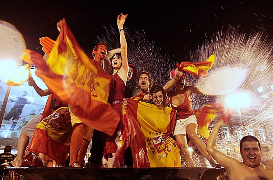 Spanish fans celebrate in a fountain in downtown Madrid after Spain defeated the Netherlands to win the World Cup soccer finall in South Africaon Sunday, July 11, 2010. Spain won 1-0. (AP Photo/Arturo Rodriguez)