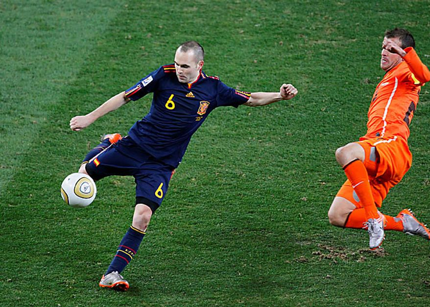 Spain's Andres Iniesta, left, scores a goal past Netherlands' Rafael van der Vaart, during the World Cup final soccer match between the Netherlands and Spain at Soccer City in Johannesburg, South Africa, Sunday, July 11, 2010. (AP Photo/Eugene Hoshiko)