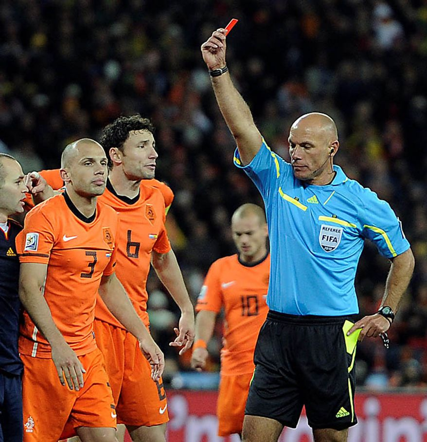 Referee Howard Webb of England, right, shows the red card to Netherlands' John Heitinga, left, during the World Cup final soccer match between the Netherlands and Spain at Soccer City in Johannesburg, South Africa, Sunday, July 11, 2010. (AP Photo/Martin Meissner)