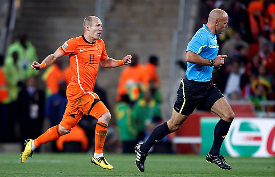 Netherlands' Arjen Robben, left, runs after referee Howard Webb, of England, right, during the World Cup final soccer match between the Netherlands and Spain at Soccer City in Johannesburg, South Africa, Sunday, July 11, 2010. (AP Photo/Luca Bruno)