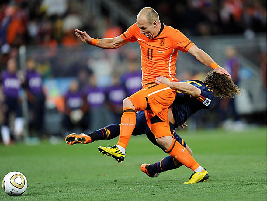 Spain's Carles Puyol, right, grabs hold of Netherlands' Arjen Robben, left, during the World Cup final soccer match between the Netherlands and Spain at Soccer City in Johannesburg, South Africa, Sunday, July 11, 2010.  (AP Photo/Daniel Ochoa de Olza)