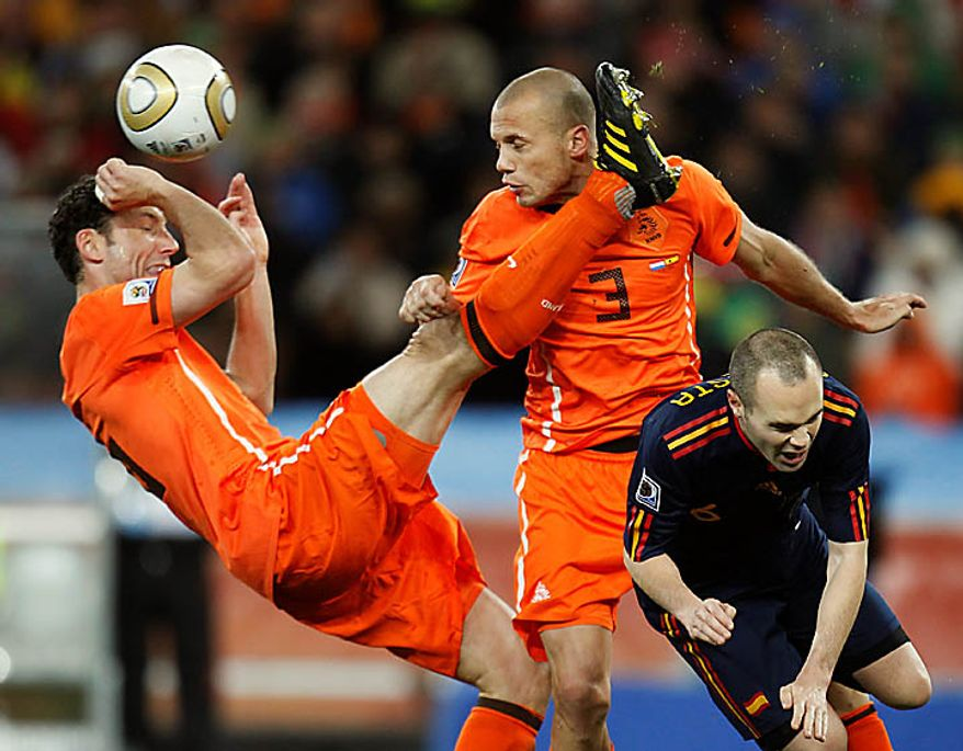 Spain's Andres Iniesta, right, competes for the ball with Netherlands' John Heitinga, center, and Netherlands' Mark van Bommel, left, during the World Cup final soccer match between the Netherlands and Spain at Soccer City in Johannesburg, South Africa, Sunday, July 11, 2010. (AP Photo/Luca Bruno)