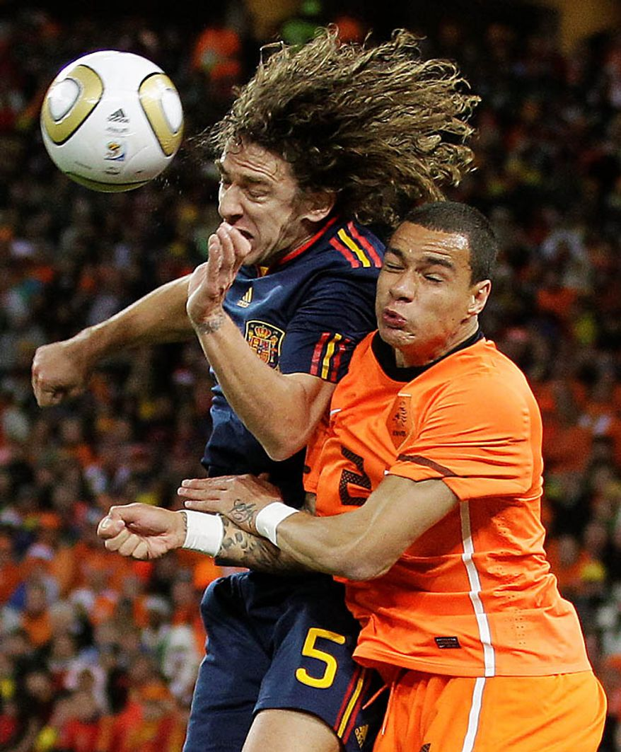 Spain's Carles Puyol, left, competes for the ball with Netherlands' Gregory van der Wiel, right, during the World Cup final soccer match between the Netherlands and Spain at Soccer City in Johannesburg, South Africa, Sunday, July 11, 2010. (AP Photo/Luca Bruno)