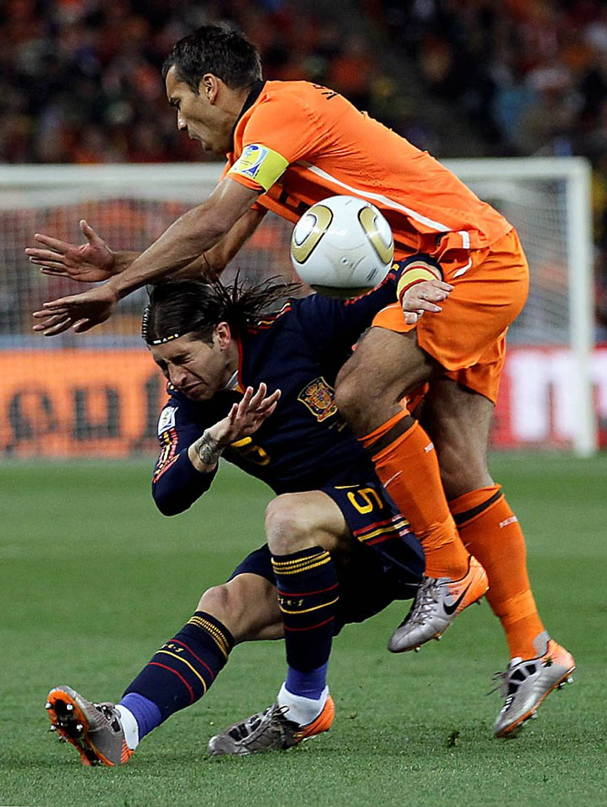 Spain's Sergio Ramos, left, and Netherlands' Giovanni van Bronckhorst fight for the ball during the World Cup final soccer match between the Netherlands and Spain at Soccer City in Johannesburg, South Africa, Sunday, July 11, 2010. (AP Photo/Ivan Sekretarev)