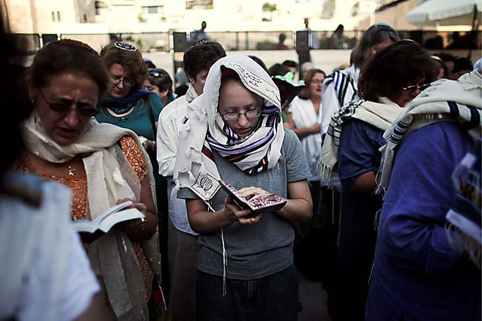 Israeli and international members of the Women of the Wall organization pray at the Western Wall, Judaism's holiest site, in Jerusalem's Old City, Monday, July 12, 2010. Anat Hoffman, the chairwoman for the Women of the Wall, was arrested for carrying a biblical scroll at a Judaism's holiest site on Monday in contravention of an Israeli high court ruling that bars women from carrying the holy texts in the area of the Western Wall, said police spokesman Micky Rosenfeld. (AP Photo/Tara Todras-Whitehill)