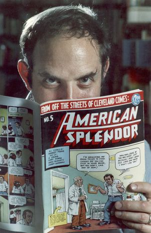"""In this 1986 file photo comic-book writer Harvey Pekar poses with a copy of his """"American Splendor"""" in his Cleveland Heights, Ohio home. (AP Photo/Mark Duncan, File)"""