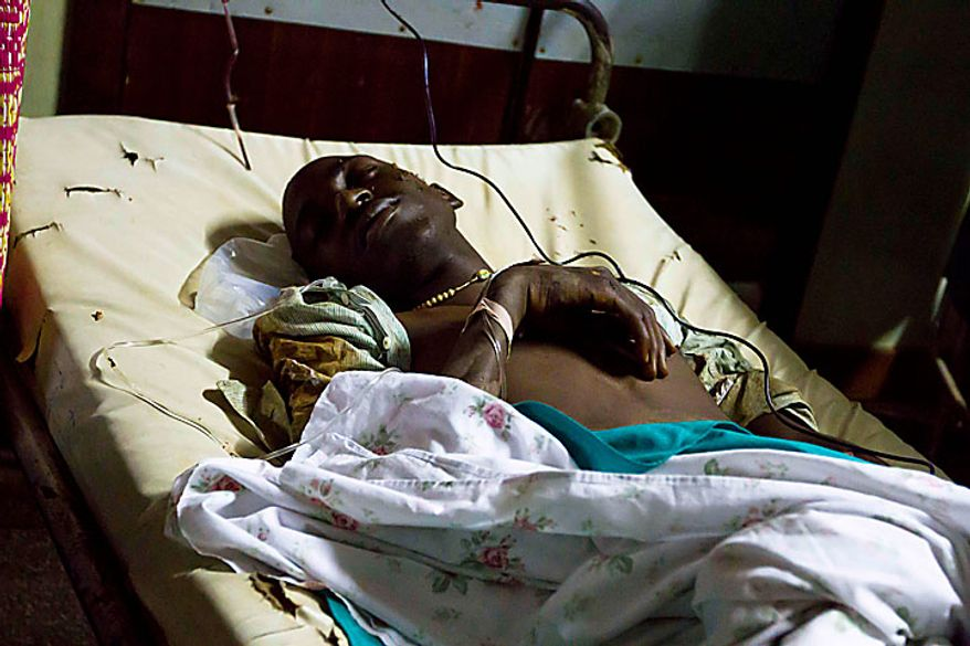 A Ugandan man lies injured in the emergency ward at the Mulago hospital, Monday, July 12, 2010, in Kampala after bombs exploded at two sites in Uganda's capital late Sunday as people watched the World Cup soccer final on TV, killing dozens. (AP Photo/Marc Hofer)