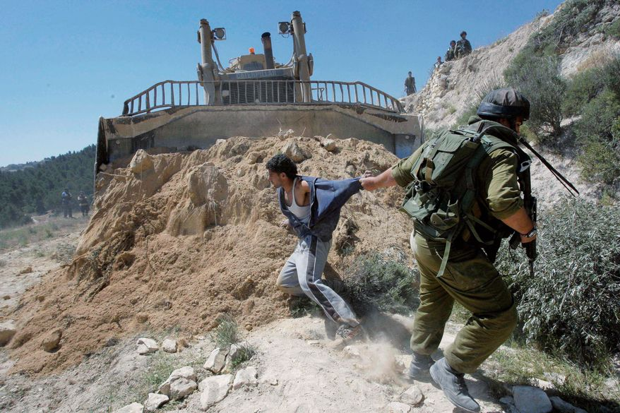 A demonstration in April erupts in a scuffle between an Israeli soldier and a Palestinian who was protesting the construction of a barrier that makes it difficult for Palestinians to reach farmland, schools and medical care. (Associated Press)