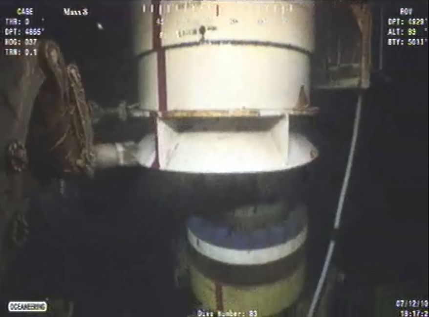 In this image taken Monday from video provided by BP PLC at 18:17 CDT, a new containment cap (left) is lowered over the broken wellhead at the site of the Deepwater Horizon oil spill in the Gulf of Mexico. Deep-sea robots swarmed around BP's ruptured oil well Monday in a delicately choreographed effort to attach the tighter-fitting cap that could finally stop crude from gushing into the Gulf of Mexico nearly three months into the crisis. (Associated Press)