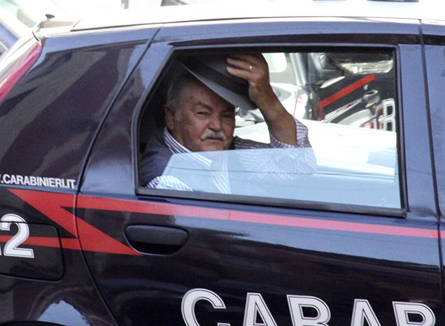 An unidentified man doffs his hat as he rides in a Carabinieri (paramilitary police) car after being arrested in Reggio Calabria in southern Italy on Tuesday, July 13, 2010, following one of the biggest operations ever against the powerful 'ndrangheta crime organization, in which 300 people were arrested, including top bosses, and million of dollars in property seized. (AP Photo/Adriana Sapone)
