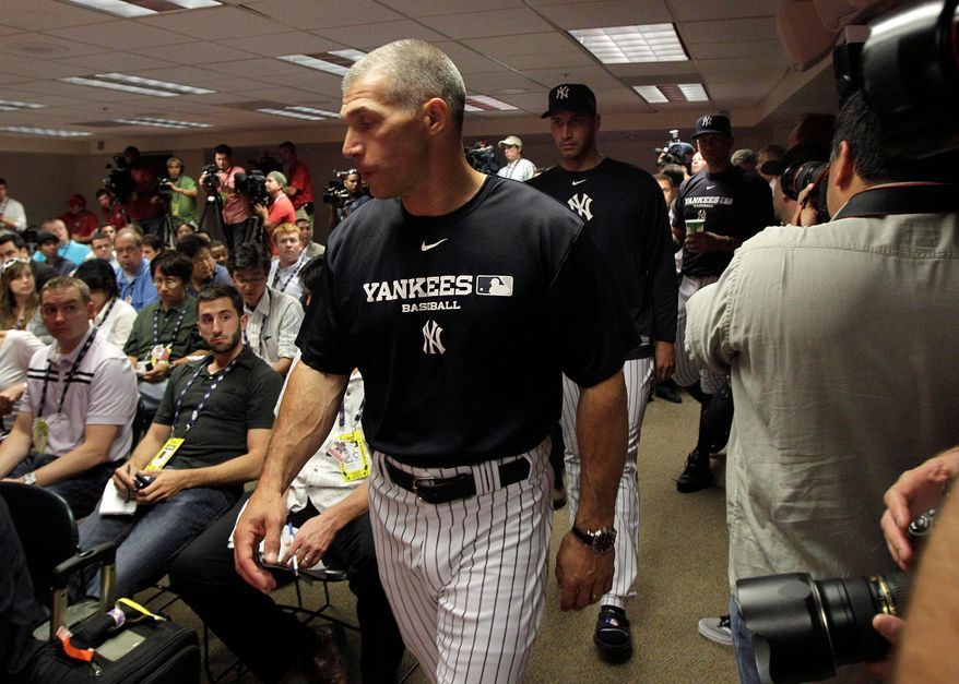New York Yankees manager Joe Girardi, with pitcher Andy Pettitte behind him, arrives for a news conference Tuesday at Angels Stadium in Anaheim, Calif. The All-Star Game there coincidently was scheduled on the same day that Yankees owner George Steinbrenner died. He rebuilt the Yankees into a sports empire with a mix of bluster and big money that polarized fans all across America but in the end won their respect. (Associated Press)