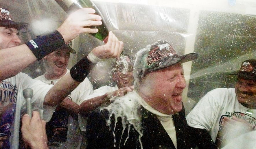 BUBBLY BALL: New York Yankees owner George Steinbrenner revels in a champagne shower after a World Series win in 1998. He bought the team in 1973 for $10 million. (Associated Press)