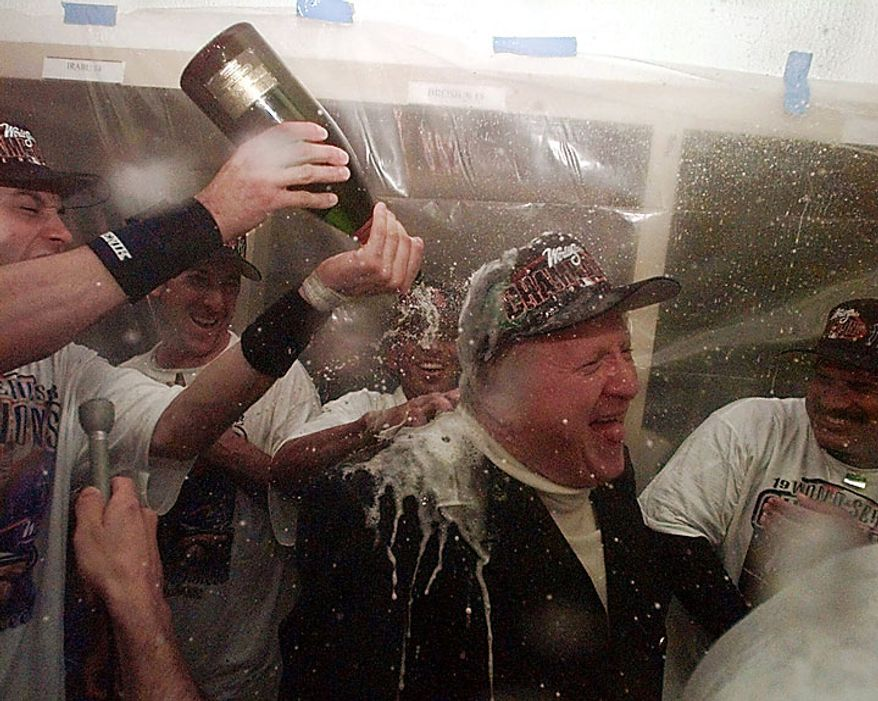 This Oct. 21, 1998, file photo shows New York Yankees owner George Steinbrenner getting a champagne shower from Andy Pettitte (left) and other Yankees in the clubhouse after Game 4 of the World Series at Qualcomm Stadium in San Diego. Steinbrenner, who rebuilt the Yankees into a sports empire with a mix of bluster and big bucks that polarized fans all across America, died Tuesday, July 13, 2010. He had just celebrated his 80th birthday July 4. (AP Photo/Pat Sullivan, File)