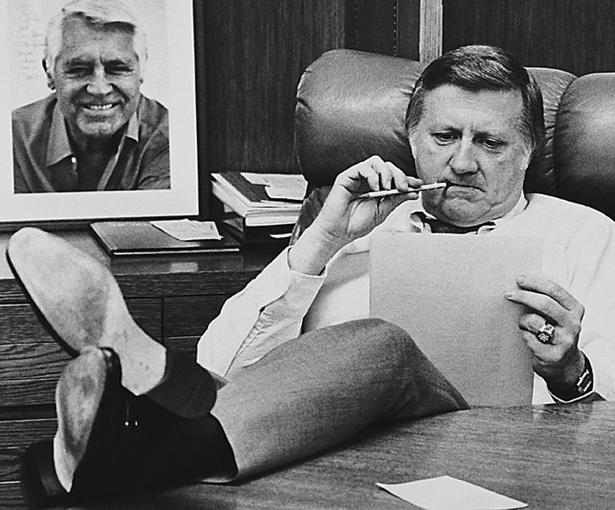 This Oct. 21, 1981, file photo shows New York Yankees owner George Steinbrenner working at his desk at Yankee Stadium in New York before Game 2 of the World Series. On the wall is an autographed photo of Cary Grant. A person close to George Steinbrenner says the Yankees owner died Tuesday morning, July 13, 2010. (AP Photo/File)