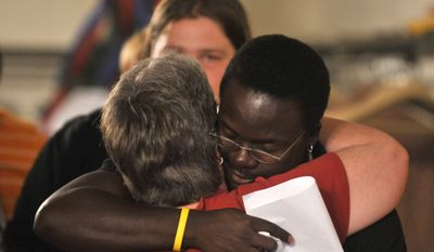 Mohammed Ssebulime is comforted at end of a prayer service at the Christ Community United Methodist Church for members of the church mission group in Uganda on Monday, July 12, 2010 in Selinsgrove, Pa. His wife Lori was with the church mission group at the time of a bomb blast at the Ethiopian Village Restaurant on Sunday. (AP Photo/Ralph Wilson)