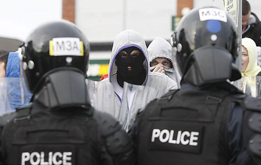 Police and nationalist protesters clash before an Orange Order march in north Belfast, Northern Ireland, Monday July 12, 2010. Police battled Irish nationalists for control of a Belfast road Monday as a day dominated by peaceful Protestant parades across Northern Ireland turned violent when night fell. (AP Photo / Niall Carson, PA)
