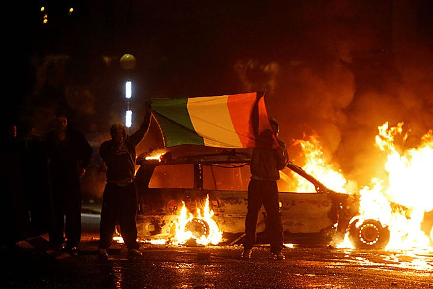 Nationalist protesters brandish the Irish tricolour flag during clashes with police in Belfast, Northern Ireland, late Monday July 12, 2010. Police struggled Monday overnight till early Tuesday, to quell rioting by Irish Catholic nationalists in several parts of Northern Ireland following a day of mass Protestant parades, an annual event that often pushes sectarian animosity past boiling point. (AP Photo)
