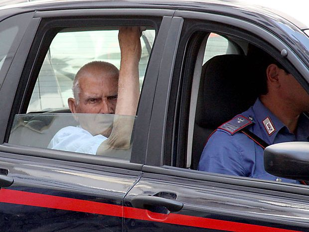 An unidentified man (left) rides in a Carabinieri (paramilitary police) car after being arrested in Reggio Calabria in southern Italy on Tuesday, July 13, 2010, following one of the biggest operations ever against the powerful 'ndrangheta crime organization, in which 300 people were arrested, including top bosses, and million of dollars in property seized. The pre-dawn raids Tuesday involved some 3,000 police across the country. Charges include murder, extortion, arms and drug trafficking, and criminal association. Investigators described the operation as one of biggest blows ever to an organization that today is considered more powerful than the Sicilian Mafia. (AP Photo/Adriana Sapone)