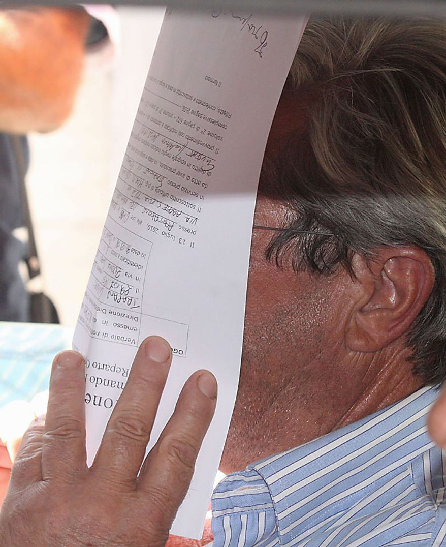 An unidentified man covers his face with an arrest warrant outside Carabinieri (paramilitary police) headquarters in Reggio Calabria in southern Italy on Tuesday, July 13, 2010, following one of the biggest operations ever against the powerful 'ndrangheta crime organization, in which 300 people were arrested, including top bosses, and million of dollars in property seized. The pre-dawn raids Tuesday involved some 3,000 police across the country. Charges include murder, extortion, arms and drug trafficking, and criminal association. Investigators described the operation as one of biggest blows ever to an organization that today is considered more powerful than the Sicilian Mafia. (AP Photo/Adriana Sapone)