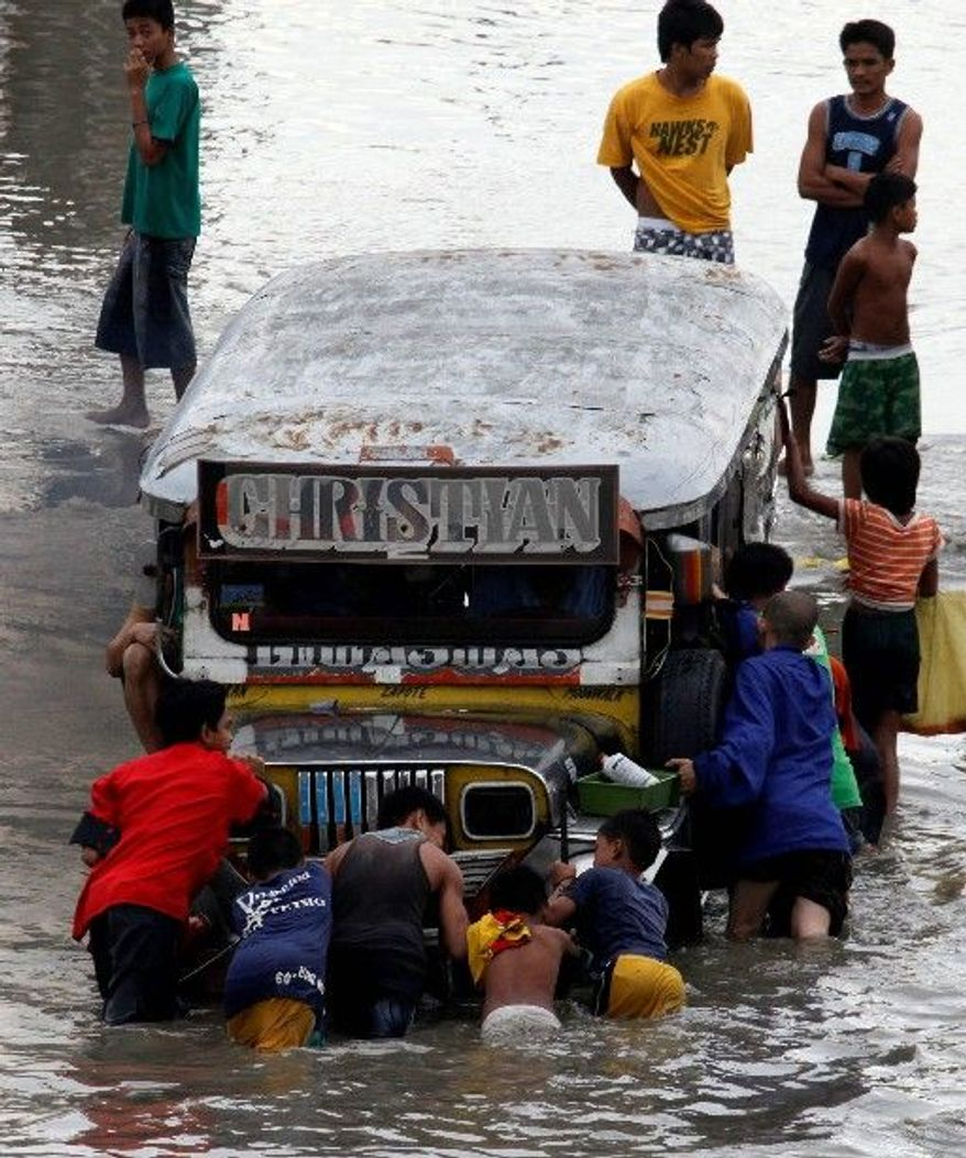 """Residents push a stalled passenger """"jeepney"""" Wednesday just hours after a typhoon blew through Manila and other provinces in the Philippines. The Philippines' first typhoon of the year, called Conson, had barreled toward the country's east coast Tuesday, prompting flight and ferry cancellations, school closures and warnings of floods and landslides. (Associated Press)"""