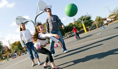 ASSOCIATED PRESS PHOTOGRAPHS Playworks program director Jabari Wimbs works with some girls playing ball during recess at Sherman Oaks Elementary School in San Jose, Calif.