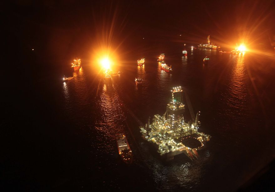 Vessels operate in the area of the Deepwater Horizon disaster on the Gulf of Mexico, Tuesday, July 13, 2010. BP officials have placed a containment cap over the leak in hopes that the flow of oil will be diminished. (AP Photo/Dave Martin)