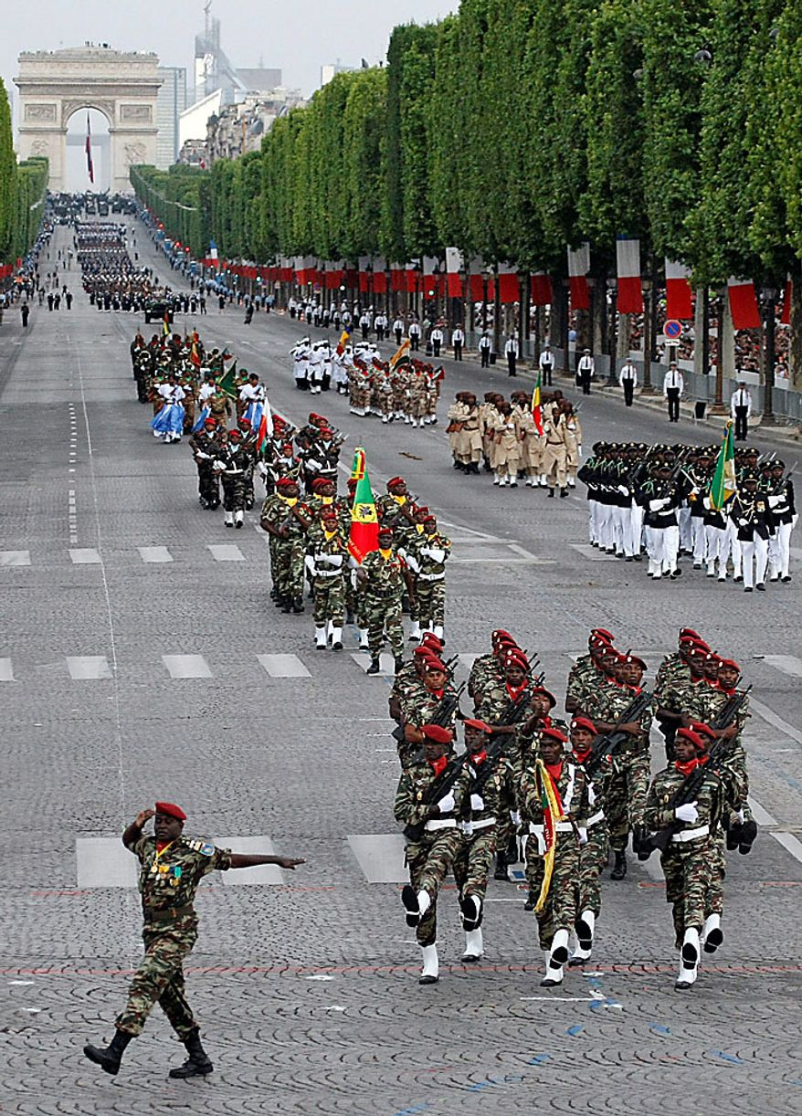 African military troops hold flags during the annual Bastille Day military parade on the Avenue des Champs-Elysees in Paris on Wednesday, July 14, 2010. (AP Photo/Francois Mori)