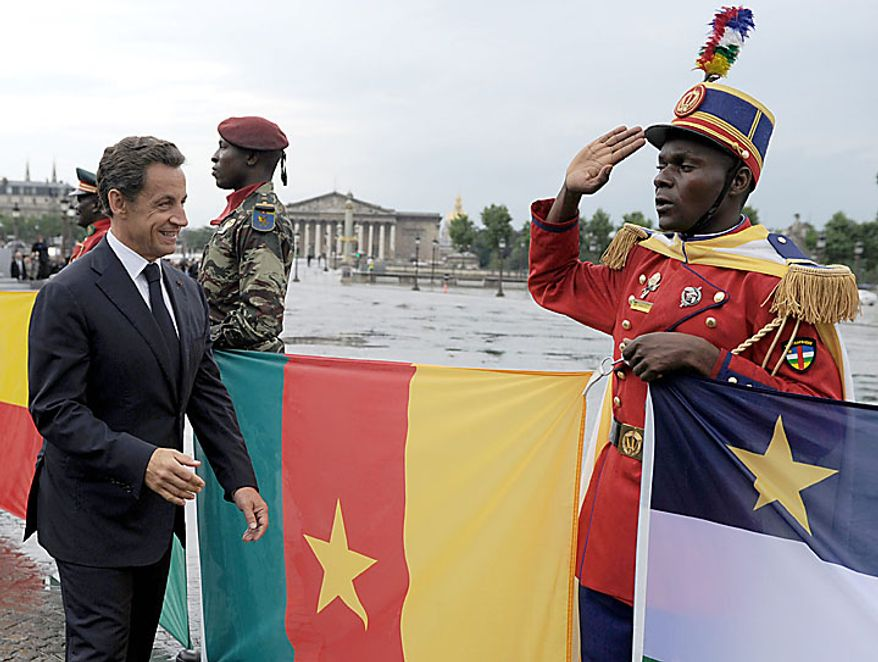 French President Nicolas Sarkozy (left) walks toward a soldier from the Central African Republic during the annual Bastille Day military parade in Paris on Wednesday, July 14, 2010. France invited former African colonies celebrating five decades of independence to take part in the parade. Mr. Sarkozy has defended himself from critics who asked whether the invitation stemmed from nostalgia for the colonial era. (AP Photo/Eric Feferberg, Pool)