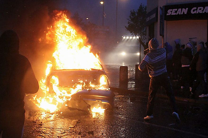 Irish nationalist rioters burn a hi-jacked car in the Ardoyne Area of North Belfast, Northern Ireland, Tuesday, July 13, 2010. Northern Ireland leaders condemned Irish nationalist rioters Tuesday who wounded 82 police officers during two nights of street clashes sparked by the province's annual parades by the British Protestant majority. (AP Photo/Liam Mc Burney)