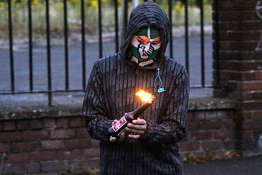 A masked youth prepares to throw a petrol bomb at police in the Ardoyne Area of North Belfast, Northern Ireland, Tuesday, July 13, 2010. Northern Ireland leaders condemned Irish nationalist rioters Tuesday who wounded 82 police officers during two nights of street clashes sparked by the province's annual parades by the British Protestant majority. (AP Photo/Liam Mc Burney)