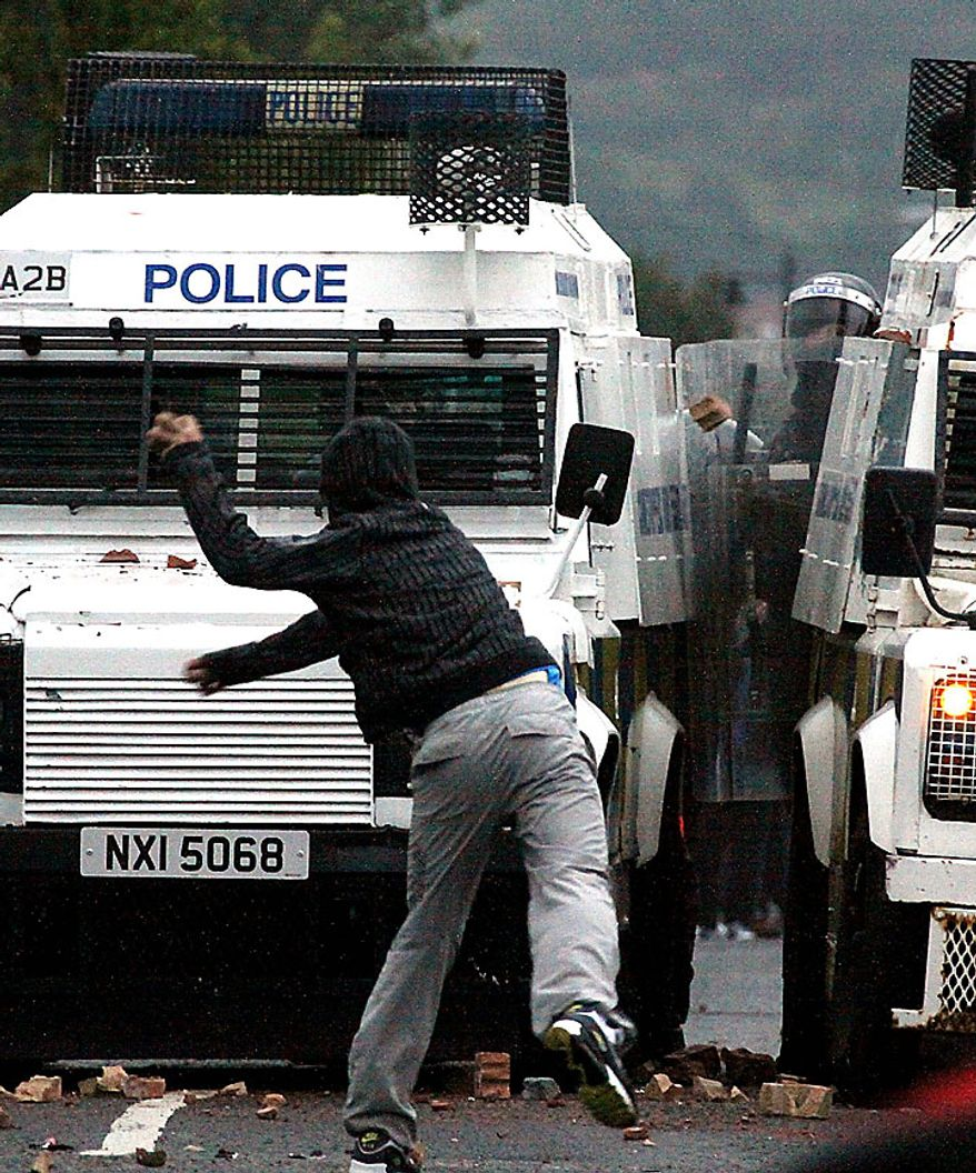 A nationalist attacks police in the Ardoyne area of North Belfast, Northern Ireland, Tuesday, July 13, 2010. Northern Ireland leaders condemned Irish nationalist rioters Tuesday who wounded 82 police officers during two nights of street clashes sparked by the province's annual parades by the British Protestant majority. (AP Photo/Liam Mc Burney)