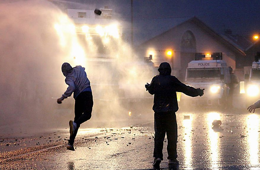 Irish nationalist rioters attack Police Service of Northern Ireland officers with water cannon in North Belfast, Northern Ireland, Tuesday, July, 13, 2010. Northern Ireland leaders condemned Irish nationalist rioters Tuesday who wounded 82 police officers during two nights of street clashes sparked by the province's annual parades by the British Protestant majority. (AP Photo/Liam Mc Burney)