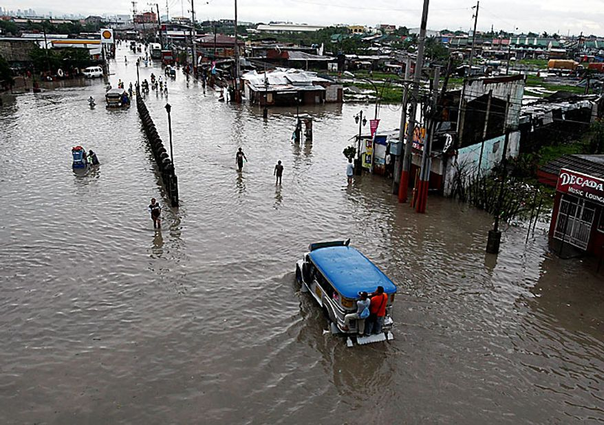 Residents of Las Pinas, Philippines, south of Manila, wade through a flooded street after typhoon Conson hit the country on Wednesday, July 14, 2010. The Philippines' first typhoon of the year prompted flight and ferry cancellations, school closures, and warnings of floods and landslides. (AP Photo/Bullit Marquez)