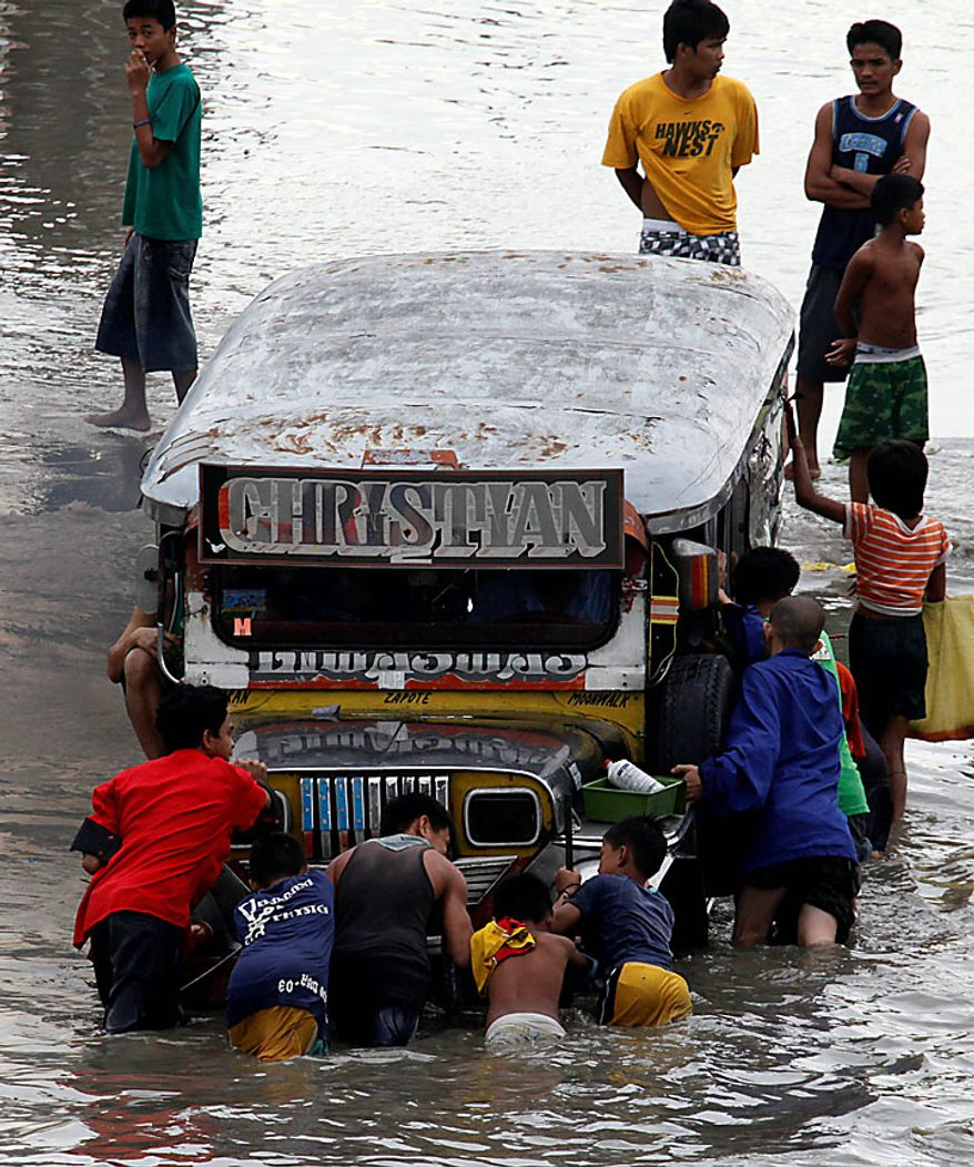 Residents push a stalled passenger jeepney in Las Pinas, Philippines, hours after typhoon Conson lashed Manila and other provinces on Wednesday, July 14, 2010. The Philippines' first typhoon of the year prompted flight and ferry cancellations, school closures, and warnings of floods and landslides. (AP Photo/Bullit Marquez)