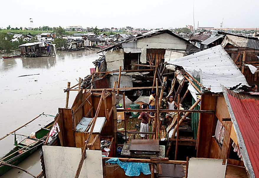 Residents fix their shanties along a coastal road after typhoon Conson hit Las Pinas, Philippines, south of Manila, on Wednesday, July 14, 2010. The Philippines' first typhoon of the year prompted flight and ferry cancellations, school closures, and warnings of floods and landslides. (AP Photo/Bullit Marquez)